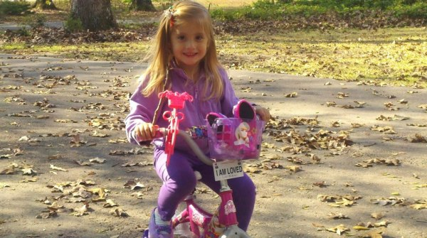 Madisyn enjoying her Barbie bike in the driveway where Dora lives!
